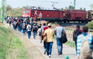 Migrants and refugees  walk toward Austria near Hegyeshalom, 168 kms west from Budapest, Hungary, Sunday,  Sept. 13, 2015. Hundreds of thousands of Syrian refugees and others are still making their way slowly across Europe, seeking shelter where they can, taking a bus or a train where one is available, walking where it isn't.   (Csaba Krizsan/MTI via AP)