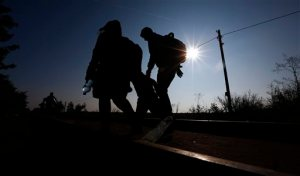 A migrant family walk to the border line between Serbia and Hungary near Roszke, southern Hungary, Sunday, Sept. 13, 2015. Hundreds of thousands of Syrian refugees and others are still making their way slowly across Europe, seeking shelter where they can, taking a bus or a train where one is available, walking where it isn't. The latest string of walkers made their way Friday from the Hungarian border across Austria toward the capital, Vienna. (AP Photo/Matthias Schrader)