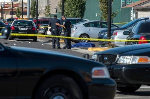 Police officers stand near the body of a victim killed in a shooting at Sacramento City College, Thursday, Sept. 3, 2015, in Sacramento, Calif. The shooting occurred in a parking lot near the baseball field on the college campus. (Renée C. Byer/The Sacramento Bee via AP)  MAGS OUT; LOCAL TELEVISION OUT (KCRA3, KXTV10, KOVR13, KUVS19, KMAZ31, KTXL40); MANDATORY CREDIT
