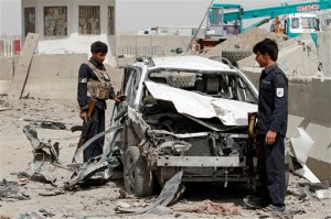 Afghan security forces inspect the site of a suicide car bombing that targeted a police checkpoint in the Daman district, on the outskirts of Kandahar, Afghanistan, Sunday, Sept. 20, 2015. An Afghan official says several people, including two police officers, were wounded in the suicide attack in Afghanistan, while at least 20 other civilians were wounded in separate attacks. (AP Photo/Allauddin Khan)