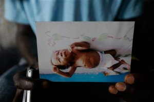 In this photo taken Tuesday, Aug. 18, 2015, nurse Donnell Tholley, 25, shows a photo of his adopted son Donnell Junior soon after his adoption, at their apartment in Freetown, Sierra Leone. Tholley adopted the boy following the death of the mother Fatu Turay last year from the Ebola virus at the hospital on the outskirts of Freetown, Sierra Leone. The Ebola epidemic killed nearly 4,000 Sierra Leoneans and left thousands of orphans. (AP Photo/Sunday Alamba)