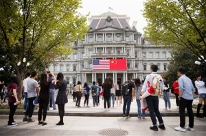 In this Thursday, Sept. 24, 2015, photo, China's flag is displayed next to the American flag on the side of the Old Executive Office Building on the White House complex in Washington, the day before a state visit by Chinese President Xi Jinping. Chinese state media characterize Xi's first state visit to the U.S. in positive terms, reporting that Xi has reassured U.S. businesses of China's healthy economy and dispelled concerns about hacking and its ambitions in the South China Sea _ the two key issues for Washington.  (AP Photo/Andrew Harnik)