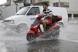 FILE - In this Sept. 23. 2014 file photo, a motorcyclist negotiates heavily flooded streets as rain falls in Miami Beach, Fla.  Expect nuisance flooding to increase along some of the nation's coasts during the next several months, federal scientists predict.  A combination of sea level rise from human caused global warming and the giant El Nino will likely combine to increase the type of minor street flooding that doesn't cause big damage, but lots of inconvenience, according to the National Oceanic and Atmospheric Administration.  (AP Photo/Lynne Sladky)