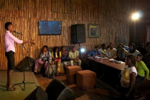 """In this photo taken Sunday, Aug. 16, 2015, a woman competes in a slam poetry competition in Lagos, Nigeria. Nigeria's young poets hurled words against the injustices plaguing the giant of Africa, from corruption to Boko Haram's insurgency, in the fifth """"War of Words"""" poetry slam. (AP Photo/Caelainn Hogan)"""