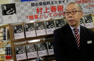 "Toru Nishine, shop manager of Kinokuniya Bookstore, speaks to journalists in front of Japanese novelist Haruki Murakami's new Japanese-language book, ""Novelist as a Vocation,"" on sale in Tokyo Thursday, Sept. 10, 2015. For best-selling Japanese novelist Murakami, finding a market for his books seems an unlikely problem. His latest work, released Thursday was 90 percent spoken for weeks ago, when major book seller Kinokuniya ordered 90,000 out of the 100,000 copies of the first printing. (AP Photo/Eugene Hoshiko)"