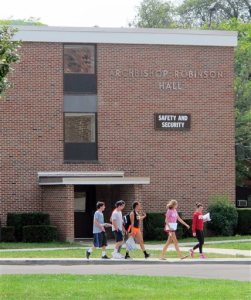 """In this Aug. 29, 2015 photo, students walk past the public safety building at St. Bonaventure University in St. Bonaventure, N.Y. Students at New York state's private colleges and universities return to campus with a new, affirmative sexual consent policy to combat campus sexual violence. A bill signed by Gov. Andrew Cuomo over the summer expands on a policy in effect at public colleges which includes a """"yes means yes"""" definition of consent requiring a clear, affirmative agreement between partners. In July, New York became the second state, after California, to write the affirmative consent standard into law for campuses.  (AP Photo/Carolyn Thompson)"""