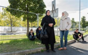 In this Sept. 22, 2015 photo, from left, Raghad, Mohammed, mother Khawla Kareem, Reem and Yaman, a refugee family from Syria, wait outside an asylum seekers shelter in Heidenau, near Dresden, eastern Germany.  (AP Photo/Matthias Rietschel)