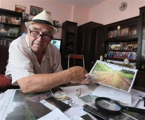 Retired miner Tadeusz Slowikowski poses for a photo at his home in Walbrzych, Poland on Tuesday, Sept. 1, 2015. The placid woodlands around the medieval castle town of Walbrzych have suddenly become the hottest spot in Poland _ as treasure hunters descend on the area in search of a mystery Nazi train said to be laden with gold.  The man considered the main living source of the legend is following the excitement from his home just a few kilometers (miles) away. Retired miner Tadeusz Slowikowski, 84, heard from a German man in the 1970s of a train that left the German city of Breslau (today Poland's Wroclaw) in the spring of 1945, as the Soviet army approached. He said the man told him the train disappeared before ever making it to Waldenburg (now Wroclaw) some 65 kilometers (45 miles) to  the west. (AP Photo/Czarek Sokolowski)