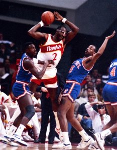 FILE - In this Dec. 28, 1988, file photo, Atlanta Hawks' Moses Malone, center, is double-teamed by New York Knicks' Gerald Wilkins, left, and Eddie Wilkins during an NBA basketball game, in Atlanta. Malone, a three-time NBA MVP and one of basketball's most ferocious rebounders, died Sunday, Sept. 13, 2015, the Philadelphia 76ers said Sunday. He was 60. (AP Photo/File)