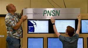 In this photo taken Thursday, Aug. 6, 2015, lab workers at the Pacific Northwest Seismic Network at the University of Washington, place a sign in their lab for an upcoming event there, in Seattle. When North America's undersea edge and a tectonic plate pushing beneath it inevitably give way to three centuries of accumulated stress, unleashing a monster earthquake and tsunami in the Pacific Northwest, the expected catastrophic loss of life and economic disruptions could be lessened by an early warning system. (AP Photo/Elaine Thompson)