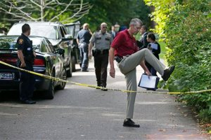 South Lake Minnetonka interim Police Chief Michael Siitari, right, climbs over the police tape to address the media Thursday, Sept. 10, 2015 in Greenwood, Minn. after five family members, including three children, were found dead in their lakeside home in an upscale western Minneapolis suburb on Thursday in what police said appeared to be a murder-suicide. (AP Photo/Jim Mone)