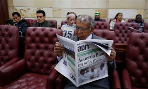 "Pedro Osuna Ramirez, 67, who says that he and his family were pushed from their land in central Colombia by rebels of the Revolutionary Armed Forces of Colombia (FARC), reads a newspaper during a hearing with victims of the guerrilla group inside Congress in Bogota, Colombia, Thursday, Sept. 24, 2015. Colombia's president and leaders of the FARC met in Havana on Wednesday, and vowed to end Latin America's longest-running armed conflict in the coming months. The newspaper's headline reads in Spanish ""Final agreement in six months."" (AP Photo/Fernando Vergara)"