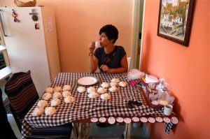 In this Aug. 26, 2015 photo, Sandra Aldama takes a break while wrapping bars of home made soap in Havana, Cuba. The church is operating in ways unimaginable in the years when the state tried to control every aspect of life in Cuba, such as the entrepreneurial training programs that imparted skills from accounting to business development that helped the Aldama family business. (AP Photo/Desmond Boylan)