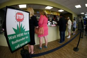 In this photograph taken with a fisheye lens Saturday, April 25, 2015, buyers make their purchases at the counter as a contingent of lawmakers, their staffers and a handful of lobbyists tour one of two retail and grow operations for both medical and recreational marijuana in northeast Denver. Colorado's unusual tax law is forcing the state to suspend taxes on recreational marijuana for one day, Sept. 16, during which a 10 percent sales tax and a 15 percent excise tax will not be collected. (AP Photo/David Zalubowski)