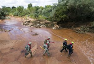 Search and rescue volunteers walk in Short Creek while looking for a missing person in Colorado City, Ariz., Wednesday, Sept. 16, 2015. Floodwaters swept away multiple vehicles in the Utah-Arizona border town, killing several people. (Michael Chow/The Arizona Republic via AP)  MARICOPA COUNTY OUT; MAGS OUT; NO SALES; MANDATORY CREDIT