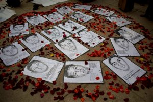 FILE.- In this March 26, 2015 file photo drawings of some of 43 missing students are surrounded by flower petals, formimg the shape of a heart, during a protest marking the six-month anniversary of their disappearance, in Mexico City. An independent report released Sunday Sept. 6, 2015 dismantles the Mexican government's investigation into last year's disappearance of 43 teachers' college students, starting with the assertion that the giant funeral pyre in which the attorney general said they were burned to ash beyond identification simply never happened.(AP Photo/Rebecca Blackwell, file)