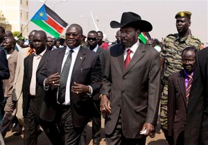 FILE - In this Tuesday, Feb. 8, 2011 file photo, South Sudanese President Salva Kiir, centre-right, is greeted by then Vice-President Riek Machar, centre-left, on Kiir's return to Juba, South Sudan, from Khartoum where he attended the formal announcement of southern Sudan's referendum results. South Sudan President Salva Kiir signed a peace deal with rebels Wednesday, Aug. 26, 2015 in a ceremony witnessed by regional leaders in the capital Juba, after 20 months since the start of fighting between loyalist forces and rebels led by his former deputy Riek Machar. (AP Photo/Pete Muller, File)