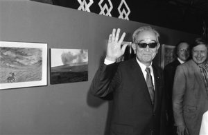 """FILE - In this Sept. 19, 1985 photo, Japanese movie director Akira Kurosawa salutes the photographers when visiting the exhibition """"About Ran"""" held at Paris Georges Pompidou National Center for Art and Culture. To mark the Busan festival's 20th anniversary, the 100 greatest Asian films of all time were selected. Yasujiro Ozu's 1953 drama """"Tokyo Story"""" was their top selection, followed by Akira Kurosawa's 1950 work """"Rashomon"""" and Wong Kar Wai's """"In the Mood for Love."""" (AP Photo/Olivier Boitet, File)"""