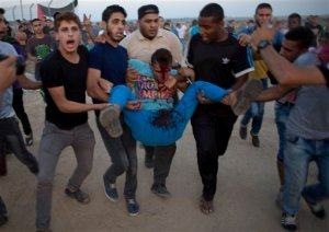 Palestinian protesters evacuate a wounded man during clashes with Israeli soldiers by the Israeli border with Gaza in Buriej, central Gaza Strip, Thursday, Oct. 15, 2015. (AP Photo/ Khalil Hamra)