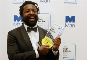 Jamaican author Marlon James holds the award after his book 'A Brief History of Seven Killings' was named as winner of the 2015 Booker Prize 2015 for Fiction, poses for photographers following the award ceremony at the Guildhall in London, Tuesday, Oct. 13, 2015.  Marlon James became the first Jamaican winner of the prestigious Booker Prize for fiction Tuesday with a vivid, violent, exuberant and expletive-laden novel based on the 1976 attempted assassination of Bob Marley.(AP Photo/Alastair Grant)