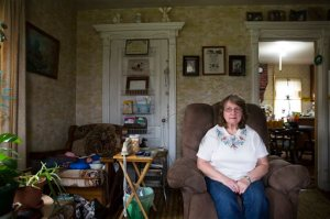 In this Friday, Oct. 9, 2015, photo, Carol Mead poses for a portrait at her home, in Montrose, Pa. Mead, 67, is retired and her husband, 70, must work at a local rock quarry to close the gap from her Social Security. For just the third time in 40 years, millions of Social Security recipients, disabled veterans and federal retirees can expect no increase in benefits next year, unwelcome news for more than one-fifth of the nation's population. (AP Photo/Brett Carlsen)