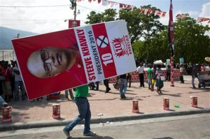 In this Oct. 10, 2015 photo, a man carries a campaign poster promoting presidential candidate Steeve Khawly, of the Bouclier political party, to a rally in Port-au-Prince, Haiti. For a few weeks at least, there's the promise of regular money to be made as human billboards, protesters for hire or paid shills for candidates amid a national election that features 54 presidential candidates, only a handful of whom have even faint name recognition among the vast majority of the population. (AP Photo/Dieu Nalio Chery)