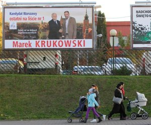 Women with children walk in front of an election poster depicting Law and Justice's  candidate Marek Krukowski and party's leader Jaroslaw Kaczynski,left, in Warsaw,  Poland, Monday, Oct. 26, 2015. According to an exit poll following the Sunday elections and released early Monday, the conservative Law and Justice won 37.7 percent of the votes, trouncing the governing pro-business Civic Platform, which took 23.6 percent. (AP Photo/Czarek Sokolowski)