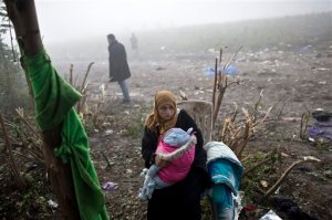 A woman holds a child as she waits to cross from Serbia into Croatia, in Berkasovo, Serbia, Friday, Oct. 23, 2015. Most migrants fleeing war and poverty in the Middle East, Asia and Africa wish to go to Germany or other wealthier countries of Western Europe. (AP Photo/Marko Drobnjakovic)