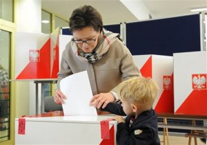 Polish Prime Minister Ewa Kopacz, assisted by her grandson Julian casts her ballot during general elections in Warsaw, Poland, Sunday, Oct. 25, 2015. Poles voted Sunday in a parliamentary election that is expected to shift power from a centrist and pro-market party to a socially conservative and somewhat Euroskeptic party that favors more welfare spending to help the poor. (AP Photo/Alik Keplicz)