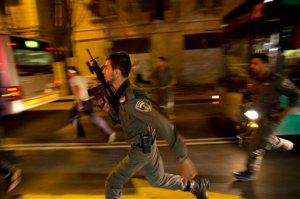 FILE - In a Wednesday, Oct. 14, 2015 file photo, Israeli policemen run looking for a possible stabbing suspect in Jerusalem. A sudden wave of stabbing attacks has spread fear in Jerusalem and much of Israel. (AP Photo/Dusan Vranic, File)