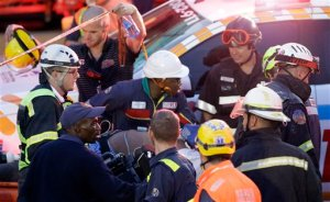 Emergency service workers and paramedics evacuate an injured man from a vehicle, which was partly crushed beneath scaffolding after a temporary bridge collapse in Johannesburg, South Africa, Wednesday, Oct. 14, 2015.  A temporary bridge that was part of a construction project collapsed onto one of South Africa's busiest highways on Wednesday.   (AP Photo/Themba Hadebe)