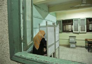 An Egyptian woman marks her ballot as her child peeks from the booth inside a polling station, during the first round of the parliamentary election, in the Boulaq El Dakrour district of Giza, near Cairo, Egypt, Sunday, Oct. 18, 2015. (AP Photo/Nariman El-Mofty)