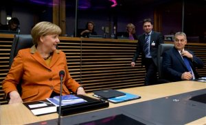 German Chancellor Angela Merkel, left, and Hungarian Prime Minister Viktor Orban, right, wait for the start of a round table meeting during an EU summit at EU headquarters in Brussels on Sunday, Oct. 25, 2015. EU leaders meet on Sunday to discuss refugee flows along the Western Balkans route. (AP Photo/Virginia Mayo)