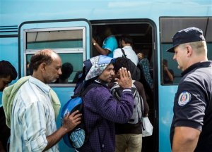Migrants get on a bus towards Bezdan, near the Serbian-Croatian border at the closed border crossing between Serbia and Hungary, in Horgos, Serbia, Thursday, Sept. 17, 2015. Croatian leaders asked the army on Thursday to be on alert after chaos erupted at the border with Serbia, where thousands of migrants and refugees have poured into the country. Some trampled over each other in a rush to get on limited buses and trains, causing dozens of injuries amid the mayhem. (Balazs Mohai/MTI via AP)