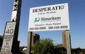 CORRECTS TO SAY THE BOSTON ORGANIZATION IS USING TEXT MESSAGING, NOT THE CAPE COD ORGANIZATION, WHOSE SIGN IS DEPICTED - In this Thursday, Oct. 8, 2015 photo, a sign for The Samaritans on Cape Cod and the Islands is posted near the Bourne Bridge, in Bourne, Mass. For decades  Samaritans have offered phone counseling to the desperate and distraught. But increasingly Samaritans, Inc., based in Boston, is turning to text messaging to engage with young people. (AP Photo/Steven Senne)