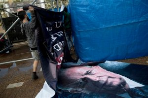 An Israeli worker hangs up a billboard with a portrait of late Israeli Prime Minister Yitzhak Rabin,  ahead of a memorial rally for the 20th anniversary of his assassination at Rabin square in Tel Aviv, Israel, Friday, Oct. 30, 2015. Twenty years after Yitzhak Rabin was gunned down by a Jewish extremist opposed to his negotiations with the Palestinians, Israel is more divided than ever over Mideast peacemaking _ and the people who opposed the assassinated premier with vitriol, led by Benjamin Netanyahu, now have a firm grip on power. (AP Photo/Oded Balilty