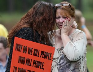 Dawn Skorcik, left, of Marietta, Ga., and Dawn Barber, of Powder Springs, Ga., comfort each other while protesting outside of Georgia Diagnostic Prison in Jackson, Ga., Tuesday evening, Sept. 29, 2015, before the execution of Kelly Gissendaner. Gissendaner was convicted of murder in the February 1997 slaying of her husband. She conspired with her lover, who stabbed Douglas Gissendaner to death. She is scheduled to die by lethal injection Tuesday night. (Ben Gray/Atlanta Journal-Constitution via AP)  MARIETTA DAILY OUT; GWINNETT DAILY POST OUT; LOCAL TELEVISION OUT; WXIA-TV OUT; WGCL-TV OUT; MANDATORY CREDIT