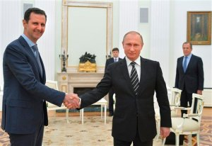 FILE - In this file photo taken on Tuesday, Oct. 20, 2015, Russian President Vladimir Putin, center, shakes hand with Syrian President Bashar Assad as Russian Foreign Minister Sergey Lavrov, right, looks on in the Kremlin in Moscow, Russia. Iran sits down with the United States, Russia, Europeans and key Arab states for the first time since the Syrian civil war began to discuss the future of the war-torn country. It will also break ground by bringing Assad's main supporter, Iran, to the same table as its regional rivals, including Turkey and Saudi Arabia, who have been backing many of the insurgent groups.  (Alexei Druzhinin, RIA-Novosti, Kremlin Pool Photo via AP, File)