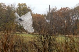 Part of an unmanned Army surveillance blimp hangs off a group of trees along County Line Road near the Montour and Lycoming county line, Wednesday, Oct. 28, 2015, after crash landing near Muncy, Pa. The blimp broke loose from its mooring in Maryland and floated over Pennsylvania for hours with two U.S. fighter jets on its tail, triggering blackouts across the countryside as it dragged its tether across power lines. (Jimmy May/Bloomsburg Press Enterprise via AP)