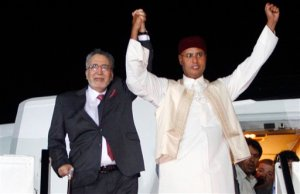"""FILE - In this Thursday, Aug. 20, 2009 file photo, Libyan Abdel Baset al-Megrahi, who was found guilty of the 1988 Lockerbie bombing, left, and son of the Libyan leader Seif al-Islam Gadhafi, right, gesture on his arrival at an airport in Tripoli, Libya. Scottish prosecutors said Thursday, Oct. 15, 2015 they have identified two Libyans as suspects in the 1988 bombing of a passenger jet over the town of Lockerbie, and want to interview them in Tripoli. Scotland's Crown office said that Lord Advocate Frank Mulholland and U.S. Attorney General Loretta Lynch had agreed """"that there is a proper basis in law in Scotland and the United States to entitle Scottish and U.S. investigators to treat two Libyans as suspects in the continuing investigation into the bombing of flight Pan Am 103."""" The unnamed Libyans are suspected of involvement with Abdel Baset al-Megrahi, the only person convicted in the attack. (AP Photo)"""