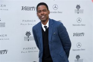 FILE - In this Jan. 4, 2015 file photo, comedian Chris Rock arrives at Variety's 10 Directors to Watch and Creative Impact Awards in Palm Springs, Calif. Rock will return to host the Oscars for a second time. The show's producers say the prolific comedian-filmmaker will be at the helm for the 88th Academy Awards next February 28. He first hosted the awards ceremony in 2005. (Photo by Rob Latour/Invision/AP, File)