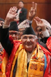Nepal's newly-appointed prime minister Khadga Prasad Oli, left, waves to the media inside the Constituent Assembly in Kathmandu, Nepal, Sunday, Oct. 11, 2015. Nepal's parliament elected Communist party leader Oli the new prime minister Sunday, thrusting him into the center of daunting challenges, from ethnic protests over the new constitution that has also upset vital neighbor India to rebuilding from April's devastating earthquake. (AP Photo/Niranjan Shrestha)