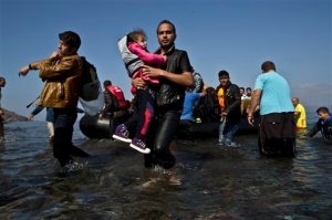 """A Syrian refugee man carrying his daughter rushes to the beach as he arrives on a dinghy from the Turkish coast to the northeastern Greek island of Lesbos, Sunday, Oct. 4 , 2015. The U.N. refugee agency is reporting a """"noticeable drop"""" this week in arrivals of refugees by sea into Greece - as the total figure for the year nears the 400,000 mark. Overall, the UNHCR estimates 396,500 people have entered Greece via the Mediterranean this year with seventy percent of them are from war-torn Syria. (AP Photo/Muhammed Muheisen)"""