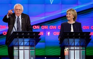 Sen. Bernie Sanders, of Vermont, left, speaks as Hillary Rodham Clinton looks on during the CNN Democratic presidential debate Tuesday, Oct. 13, 2015, in Las Vegas. (AP Photo/John Locher)