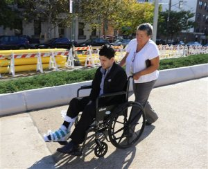 Suspended Linden, N.J., Police Officer Pedro Abad is pushed toward the courthouse in a wheelchair in the Staten Island borough of New York, Thursday, Oct. 29, 2015, for an appearance on drunken driving charges. During the proceedings, Abad's attorney said his client may have been drugged at a strip club before crashing head-on into a tractor-trailer on March 20, 2015. The accident killed two of his passengers and injured a third. (Anthony DePrimo/Staten Island Advance, via AP) NO SALES,  TV OUT,  MAGS OUT, NYC LOCALS OUT; MANDATORY CREDIT