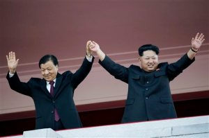 FILE - In this Saturday, Oct. 10, 2015 file photo, North Korean leader Kim Jong Un, right, waves his hands with Chinese official Liu Yunshan during a military parade to mark the 70th anniversary of the North's ruling party and trumpet Kim's third-generation leadership in Pyongyang, North Korea. The two men raised their clasped hands above their heads like a pair of victorious athletes, as international media and tens of thousands of North Koreans looked on. The gesture during a high-profile celebration in Pyongyang seemed designed to scotch appearances that their countries have been drifting apart. (AP Photo/Wong Maye-E, File)