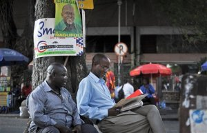 Tanzanians sit next to a tree, underneath an election poster for ruling party presidential candidate John Magufuli, as they await election results in Dar es Salaam, Tanzania Tuesday, Oct. 27, 2015. The presidential race is the most tightly contested since Tanzania became independent in 1961, with the ruling party being challenged by a former member who was recently the country's prime minister. (AP Photo/Khalfan Said)