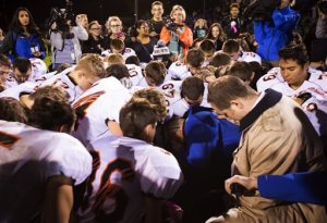 FILE - In this Friday, Oct. 16, 2015, file photo, Bremerton High assistant footbal coach Joe Kennedy, center in blue, kneels and prays after his team lost to Centralia in Bremerton, Wash. The coach of a Washington state high school football team who prayed at games despite orders from the school district to stop has been placed on paid administrative. Bremerton School District officials said in a statement late Wednesday, Oct. 28, 2015, that assistant football coach Joe Kennedy's leave was necessitated because of his refusal to comply with district directives that he refrain from engaging in overt, public religious displays on the football field while on duty as a coach.   ( Lindsey Wasson/The Seattle Times via AP) OUTS: SEATTLE OUT, USA TODAY OUT, MAGAZINES OUT, TELEVISION OUT, SALES OUT. MANDATORY CREDIT TO: LINDSEY WASSON / THE SEATTLE TIMES.