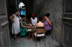 FILE - In this Sept. 16, 2015, file photo, women play dominoes in a building courtyard in Old Havana, Cuba. The sprouting of high-end clubs and bars around Havana is unsettling to many in Cuba who grew up believing in equality as a tenet of the revolution, and now see foreigners and wealthy Cubans spending many times in one night the roughly $30 monthly salary of the average Cuban state worker. (AP Photo/Ramon Espinosa,File)