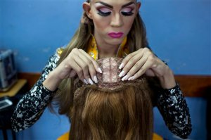 In this Oct. 18, 2015 photo, contestant Jorge Solano, Miss Gay Cojedes, inspects his wig backstage at the ninth annual Miss Gay Venezuela beauty pageant in Caracas, Venezuela. Some contestants can afford to use wigs made of real, natural hair, while others use synthetic wigs. (AP Photo/Ariana Cubillos)